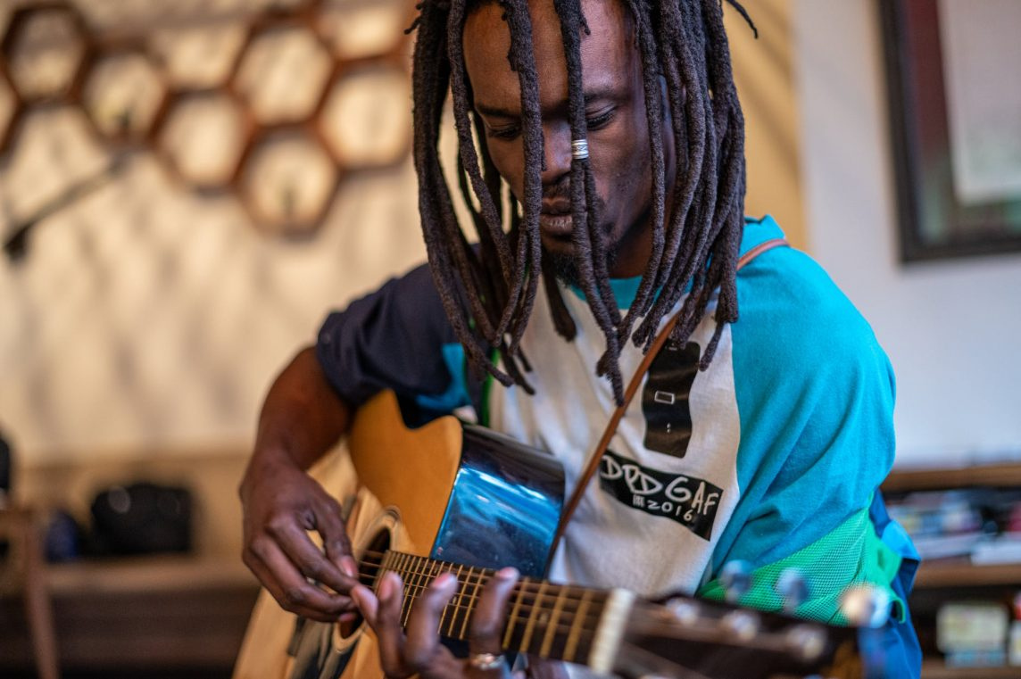 focused black man playing guitar in studio
